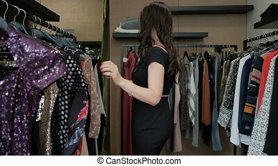 In the boutique, a woman tries on a dazzlingly sparkling...