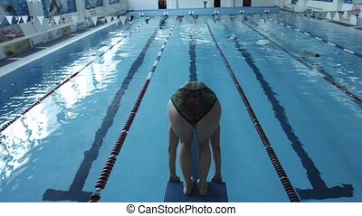 Girl swimmer jumps into the pool. The view from the back - A...