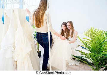 Woman choosing wedding dress in shop with her friends