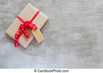 Gift with red ribbon and tag on a concrete table - Gift with...