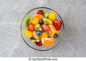 Fruit salad in crystal bowl on gray stone. Top view