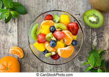 Fruit salad in crystal bowl on wooden table. Top view