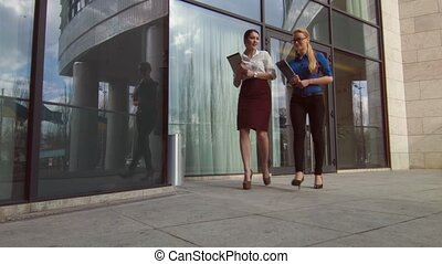 Positive businesswomen walking near office center - Friends...