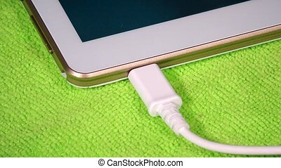 Hand unplug white micro usb cable from smart tablet computer...