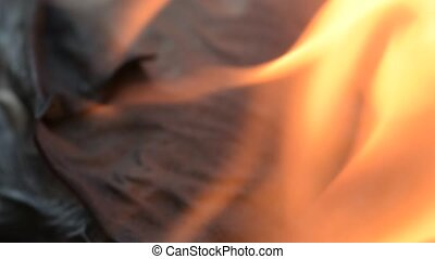 Burning paper in fire, closeup. Slider shot, left to right...