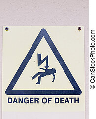 a white yellow and black close up sign on the wall saying danger of death with electric bolt and dead man in triangle safety warning electrics electrified