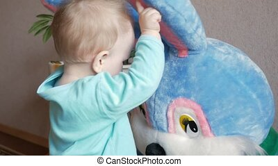 An attractive boy 2 years old plays with a huge plush rabbit at home. Kid shows eyes and touches the ears