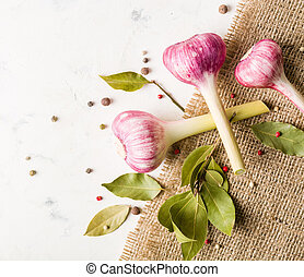 Garlic purple with a stem on the background of coarse burlap.