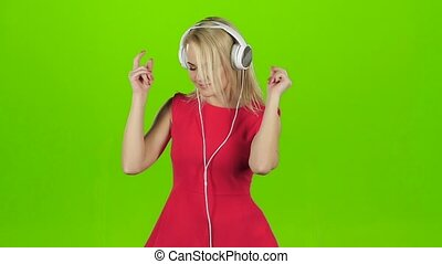 Sexy girl in red dress dancing in headphones, green screen -...