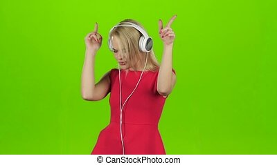 Blonde girl in red dress dancing in headphones, green screen...