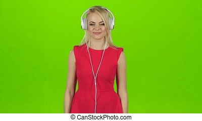 Blonde in a red dress dancing in headphones, slow motion -...