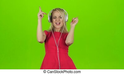Sexy girl in red dress dancing in headphones, slow motion -...