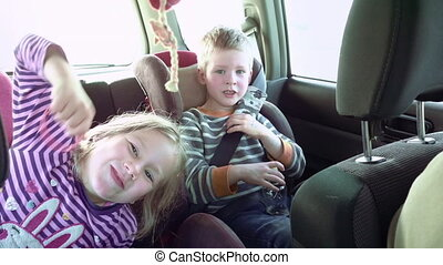 Smiling and laughing children in a car seats - Cute fun...