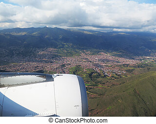 Engine of the plane on blue sky, clouds and mountains