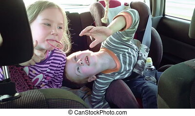Smiling and laughing children in a car seats - Happy...