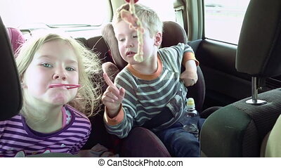 Smiling and laughing children in a car seats - Happy fun...