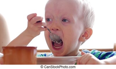 Baby 2 years old eats porridge with a spoon. Mom sits next...