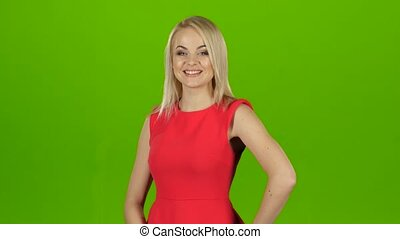 Blond girl in red dress posing in front of camera, bright...