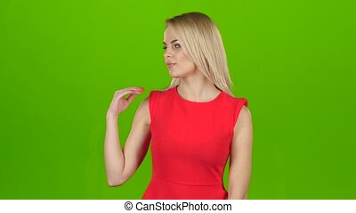 Lady in red on green screen background shows her hand, shows...