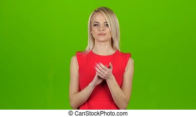 Girl reluctant applauds with her both hands. Green screen...