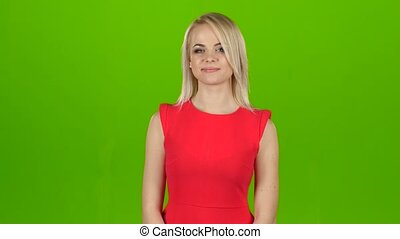 Girl in red on green screen background shows her hand, shows...