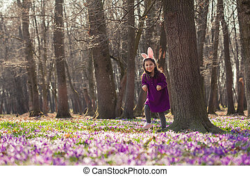 Little girl with banny ears in spring park