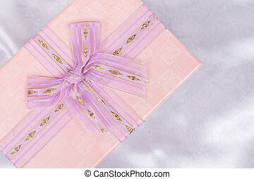 Pink gift box with bow over white satin