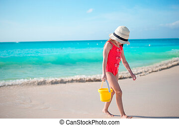Adorable little girl walking along white sand Caribbean...