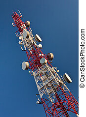 Telecommunication mast with microwave link antennas over a blue sky.