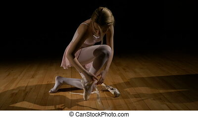 Blonde ballerina untying shoes and sitting on the floor...