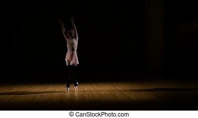 Graceful ballerina practicing ballet in the studio