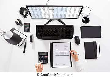 Elevated View Of A Businesswoman Calculating Invoice On Desk...