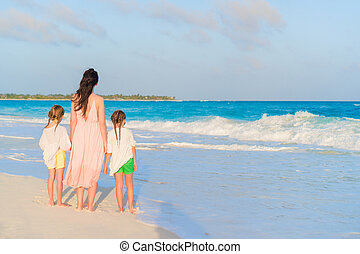 Adorable little girls and young mother on white beach on sunset