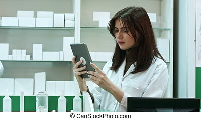 Female pharmacist with digital tablet searching for...