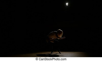 Silhouette of a sexy attractive woman dancing in the dark