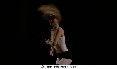 Attractive blonde woman dancing on black