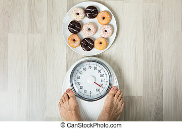 Dish Of Donuts And Person Measuring His Weight - A Person's...