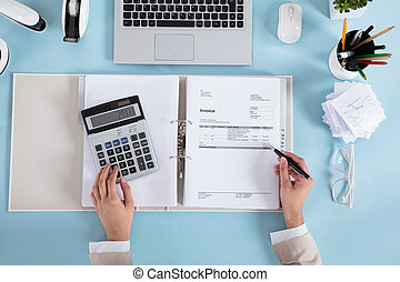 Businesswoman Calculating Invoices - Elevated View Of A...
