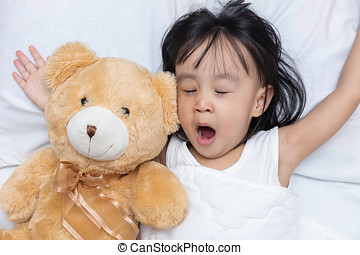 Asian little Chinese girl sleeping with teddy bear on the...