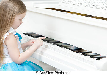 Little girl plays the piano. - Cute little girl with long...