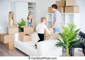 Family packing cardboard boxes - Happy family of five is...