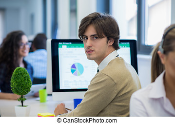Multiethnic group of happy business people working with laptop computer in office