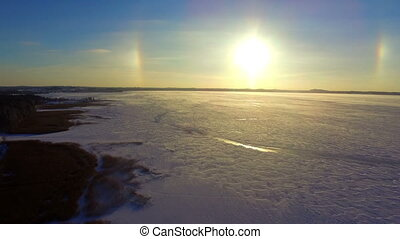 Drone flight over the snowy frozen lake at sunset
