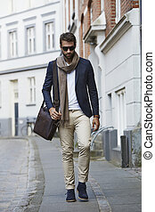 City life - Man in shades and scarf walking through city