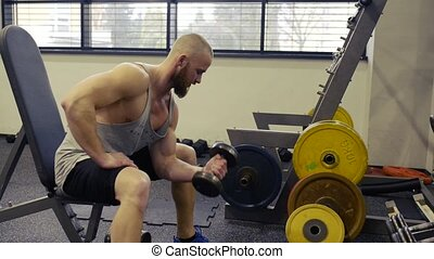 Handsome man in gym, working his arms with weights - Young...