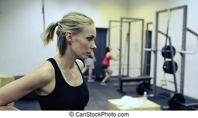 Beautiful blond woman in black singlet in gym resting -...