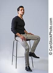 Black haired latino man sitting on stool - Brown eyed, black...