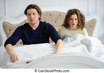 The young couple has overslept. The man and the woman sit in...