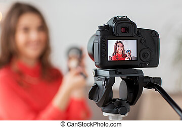 woman with bronzer and camera recording video - blogging,...