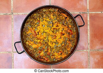 Paella rice recipe Mediterranean Spain round pan on clay...